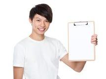 Manifestazione asiatica del giovane con la pagina in bianco della lavagna per appunti Immagini Stock
