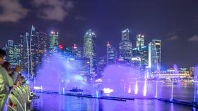 Manifestazione dell'acqua e della luce lungo passeggiata davanti al timelapse di Marina Bay Sands archivi video