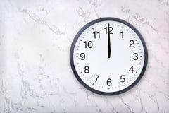 Manifestazione dell'orologio di parete i dodici in punto su struttura di marmo bianca Mezzogiorno o mezzanotte di manifestazione  immagini stock libere da diritti