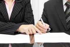 Manifestazione della donna di affari un uomo d'affari per firmare un accordo Fotografie Stock Libere da Diritti