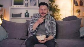 Manifestazione di sorveglianza della persona allegra sull'indicare di risata della TV allo schermo che mangia popcorn stock footage