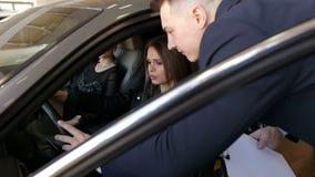 Manifestazioni del consulente in materia di vendite all'ragazze una nuova automobile da comprare stock footage