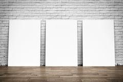 Manifesti bianchi sul pavimento di legno e del muro di mattoni Fotografia Stock Libera da Diritti