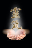 Manifesting Reiki Kanji Symbol. Female healer with cupped hands emerging from darkness and a Reiki Kanji symbol floating above royalty free stock image