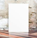 Manifesto in bianco bianco nella parete del cemento della crepa e in floo di legno diagonale Immagini Stock