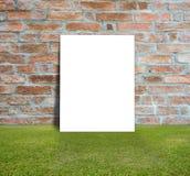Manifesto in bianco con il muro di mattoni ed il prato inglese verde Immagini Stock