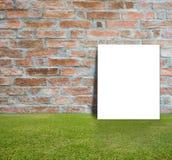 Manifesto in bianco con il muro di mattoni ed il prato inglese verde Fotografia Stock Libera da Diritti