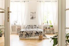 Manifesto in bianco e nero sopra il letto con i cuscini modellati nel brigh Fotografie Stock Libere da Diritti