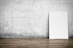 Manifesto bianco sul pavimento di legno e del muro di cemento Immagini Stock Libere da Diritti