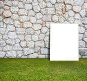 Manifesto che sta con la parete di pietra ed il campo verde Immagine Stock