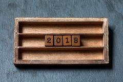 manifesto dell'invito della cartolina d'auguri di 2018 anni Scatola d'annata, cubi di legno con le lettere di vecchio stile Pietr Fotografia Stock