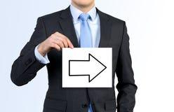 Manifesto della tenuta dell'uomo d'affari con la freccia Immagini Stock