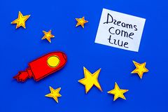 Manifesto motivazionale I sogni si avverano l'iscrizione della mano al fondo blu dell'universo con la vista superiore delle stell Fotografie Stock Libere da Diritti