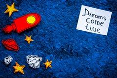 Manifesto motivazionale I sogni si avverano l'iscrizione della mano al fondo blu dell'universo con lo spazio della copia di vista Fotografia Stock Libera da Diritti