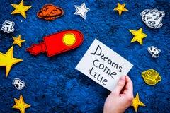Manifesto motivazionale I sogni si avverano l'iscrizione della mano al fondo blu dell'universo con lo spazio della copia di vista Immagini Stock Libere da Diritti