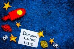 Manifesto motivazionale I sogni si avverano l'iscrizione della mano al fondo blu dell'universo con lo spazio della copia di vista Immagini Stock