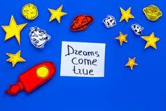 Manifesto motivazionale I sogni si avverano l'iscrizione della mano al fondo blu dell'universo con lo spazio della copia di vista Immagine Stock Libera da Diritti