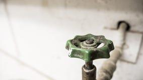 Maniglia d'annata del rubinetto, contro il muro di mattoni bianco Fotografia Stock