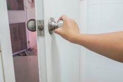 Maniglia della porta del bagno della tenuta della donna per l'uscita fotografie stock libere da diritti