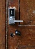 Maniglia di porta elettronica con i bottoni numerici sulla vecchia porta Immagine Stock