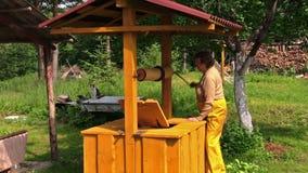 Maniglia gialla rurale di legno di giro della nonna bene in campagna stock footage