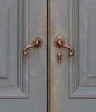 Maniglie bronzee antiquate della porta grigia Fotografie Stock Libere da Diritti