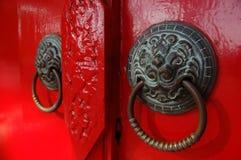 Maniglie di porta sulla porta rossa immagini stock