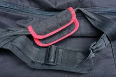 Maniglie nere e cablaggi di rosso fatti del panno su uno zaino fotografie stock libere da diritti