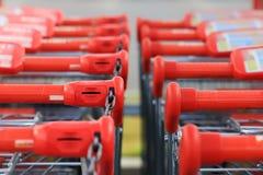 Maniglie rosse dei carrelli di acquisto Immagine Stock
