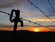 Manija de la bomba, alambre de púas y puesta del sol rural Imagen de archivo