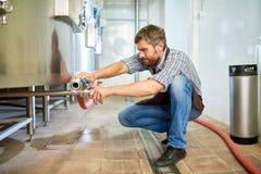 Manija técnica hermosa de la transferencia del cervecero en la fábrica imagen de archivo libre de regalías