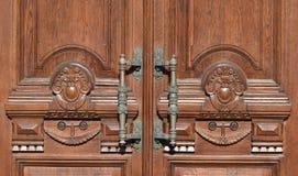 Manijas de bronce antiguas en una puerta de madera vieja imagenes de archivo