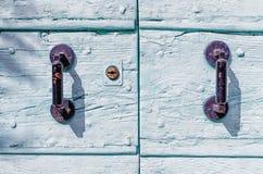 Manijas oxidadas del hierro en una puerta de madera pintada Foto de archivo libre de regalías