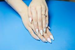 maniküre Die Frau säubert und malt Nägel Die Frau verarbeitet Nägel auf Händen ein Lack Shelak Gel, ein Lack, acryle setzend Stockfotografie