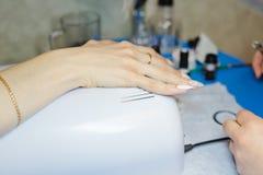 maniküre Die Frau säubert und malt Nägel Die Frau verarbeitet Nägel auf Händen ein Lack Shelak Gel, ein Lack, acryle setzend Lizenzfreie Stockfotos