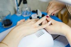 maniküre Die Frau säubert und malt Nägel Die Frau verarbeitet Nägel auf Händen ein Lack Shelak Gel, ein Lack, acryle setzend Stockbilder