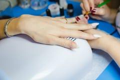 maniküre Die Frau säubert und malt Nägel Die Frau verarbeitet Nägel auf Händen ein Lack Shelak Gel, ein Lack, acryle setzend Lizenzfreie Stockbilder