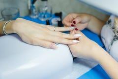maniküre Die Frau säubert und malt Nägel Die Frau verarbeitet Nägel auf Händen ein Lack Shelak Gel, ein Lack, acryle setzend Lizenzfreies Stockbild