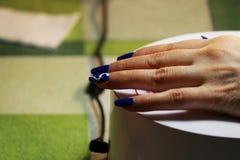 Maniküre durchgeführt vom Studenten die Hand liegt auf einer speziellen Ultraviolett-Lampe Blaues Ende mit einem gemalten weißen  lizenzfreie stockfotos