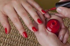 Maniküre mit rote polnische Nägel Stockfotos