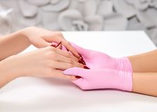 Maniküre am Schönheitssalon Meister hält client& x27; s-Handhandnahaufnahme Rosa Handschuhe, roter Nagellack lizenzfreies stockbild