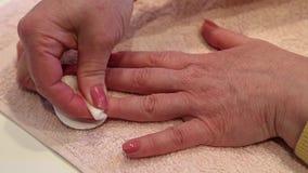 Manikürebehandlung im Schönheitssalon Frau entfernt Lack vom Nagel stock footage