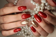 Maniküren Sie helles Rot der Nägel weitgehend und Goldfarbe stockfotografie