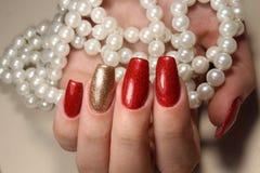 Maniküren Sie helles Rot der Nägel weitgehend und Goldfarbe stockbilder
