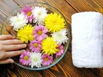 Maniküren Sie mit Fuß Badekurort von den Blumen auf hölzernem Hintergrund und weißem Tuch lizenzfreie stockfotografie
