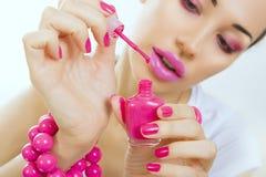 Maniküreprozeß - schönes Mädchen macht rosa Maniküre lizenzfreie stockfotografie