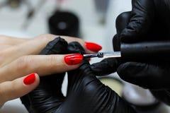Manik?respezialist in der schwarzen Handschuhsorgfalt ?ber Handn?gel Manik?rist malt N?gel mit rotem Nagellack stockbilder