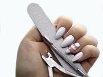 Manikürewerkzeuge - Schieber, Häutchenquetschwalze und Puffer in der Hand mit langen weißen Nägeln lizenzfreies stockbild