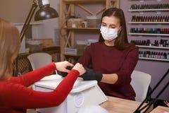 Manikürist überprüfen die Hände des Kunden im Schönheitssalon stockfoto