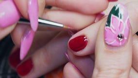 Manikürist malt Nägel mit rotem Lack stock video